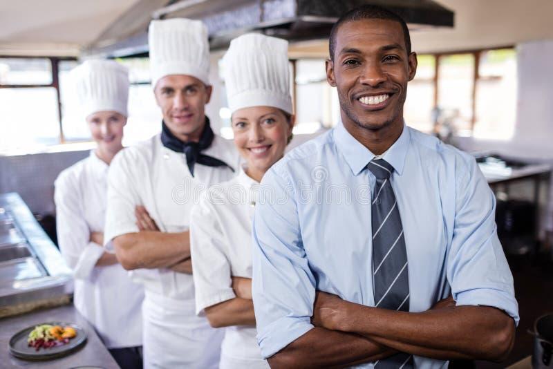 Группа в составе шеф-повара и положение менеджера с оружиями пересеченными в кухню стоковое фото rf