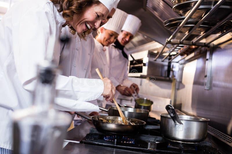 Группа в составе шеф-повар подготавливая еду в кухне стоковое фото rf
