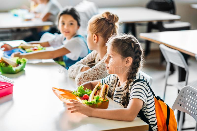 группа в составе школьницы принимая обед в школу стоковое изображение