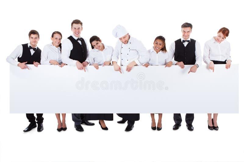 Группа в составе штат ресторанного обслуживании держа пустое знамя стоковое изображение