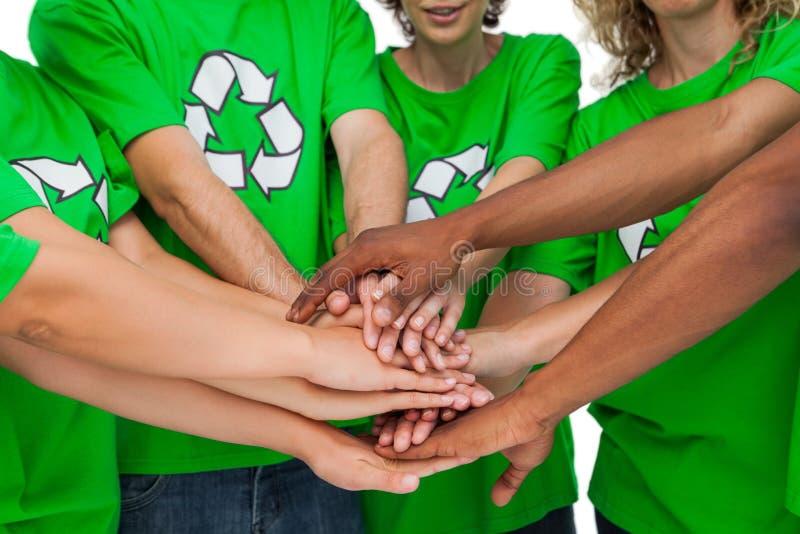 Группа в составе экологические активисты кладя руки совместно стоковые фотографии rf