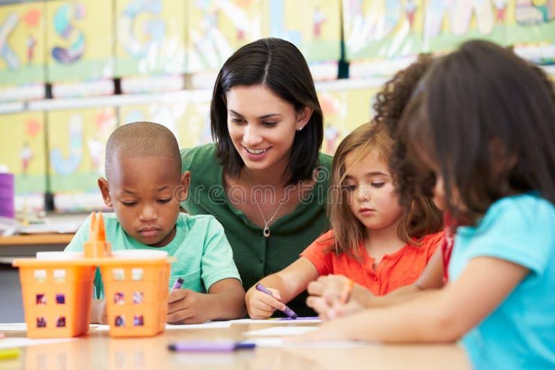 Группа в составе элементарные дети времени в художественном классе с учителем стоковое фото rf