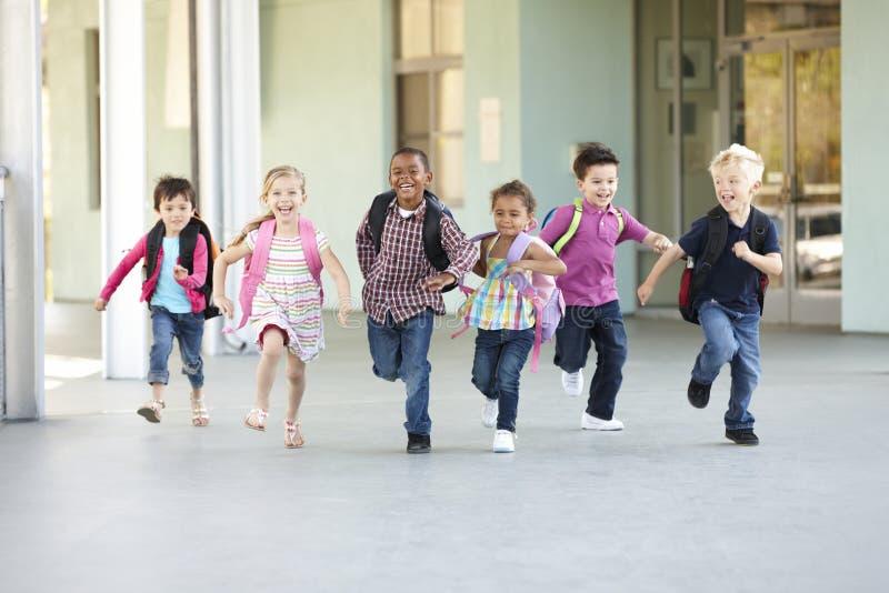 Группа в составе элементарные школьники времени бежать снаружи стоковое фото rf