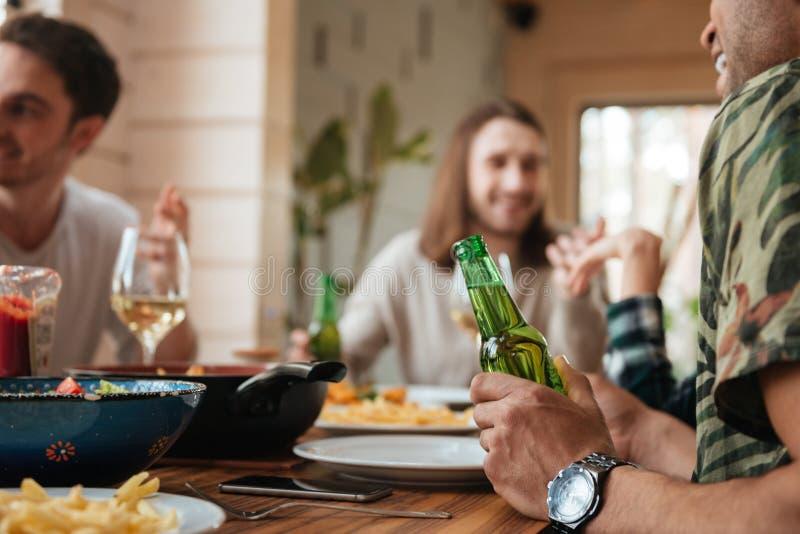 Группа в составе люди говоря и выпивая пиво на таблице стоковые фото