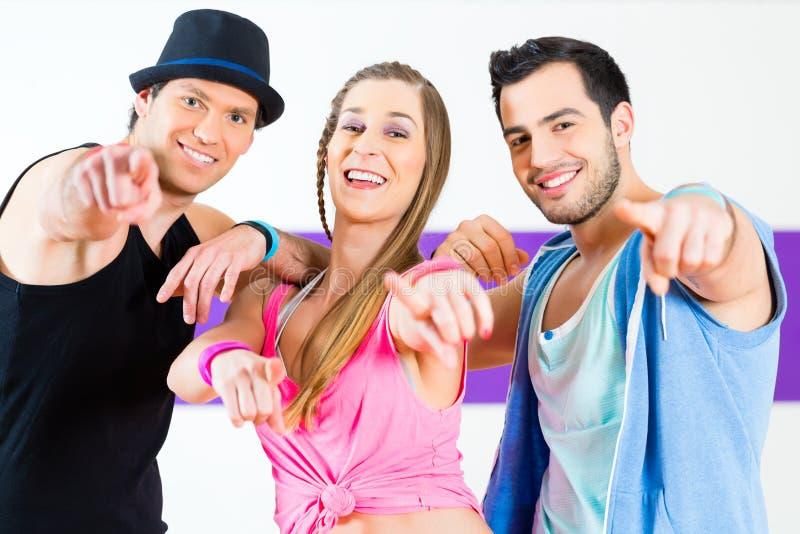 Группа в составе люди и женщины танцуя zumba стоковое изображение