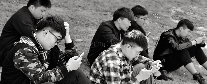 Группа в составе люди Китаев используя их мобильные телефоны outdoors стоковые изображения rf