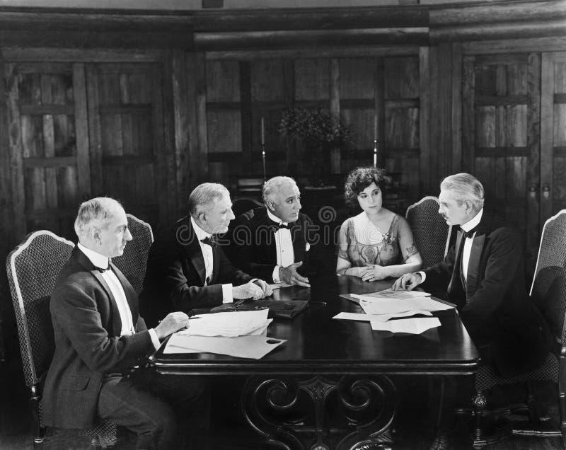 Группа в составе люди сидя с молодой женщиной в зале заседаний правления (все показанные люди более длинные живущие и никакое иму стоковые фотографии rf