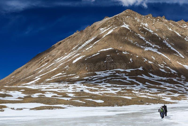 Группа в составе backpacker идет на замороженное реку на пути к священной горе Kailash, Тибету стоковое изображение