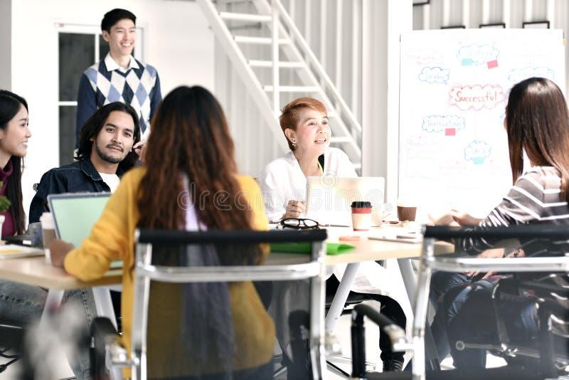 Группа в составе businesspersons вскользь обсуждая работу и беседуя в вскользь установке стоковое изображение rf