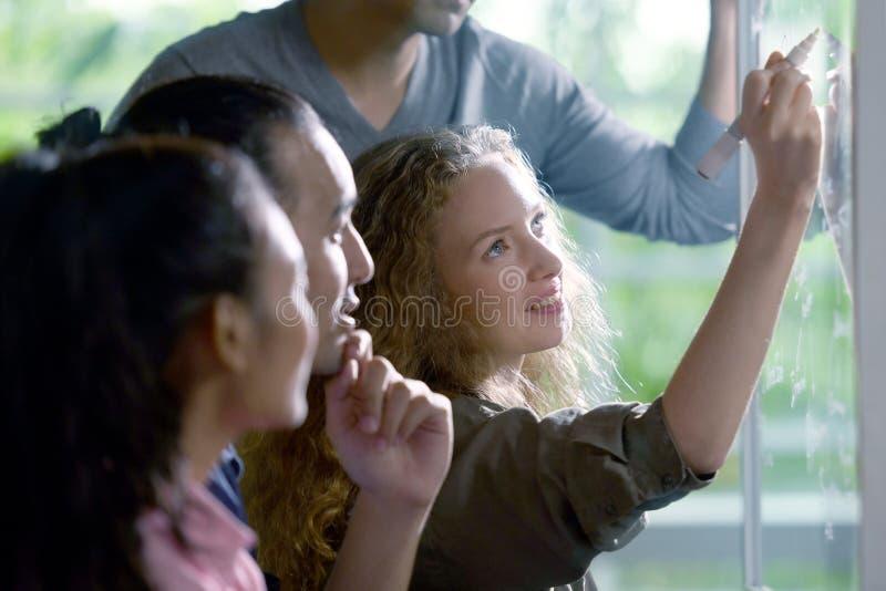 Группа в составе businesspersons обсуждая работу и используя стеклянную доску стоковое изображение