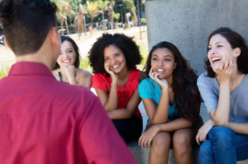 Группа в составе multi этнические девушки flirting с одним парнем стоковое изображение rf