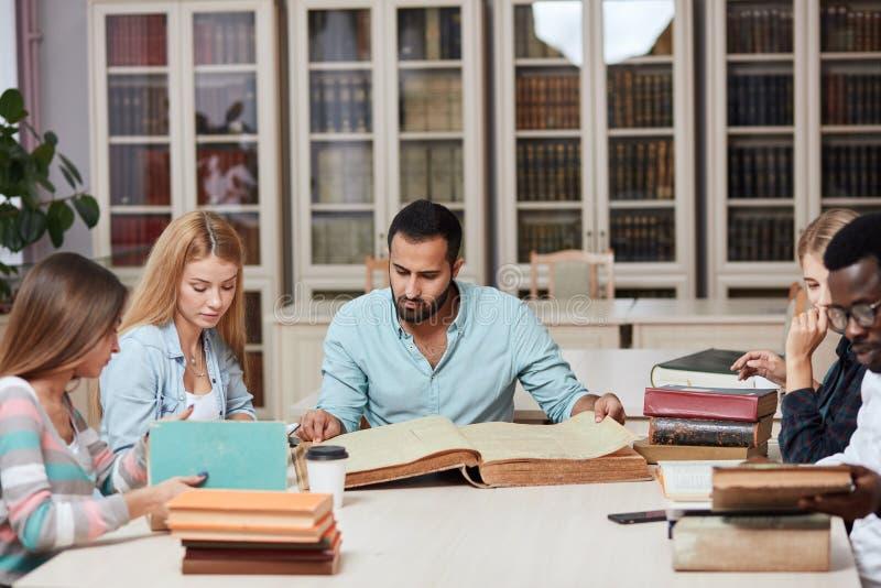 Группа в составе multiracial люди изучая с книгами в библиотеке колледжа стоковое фото