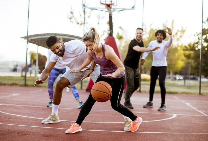 Группа в составе multiracial молодые люди играя баскетбол outdoors стоковое изображение rf