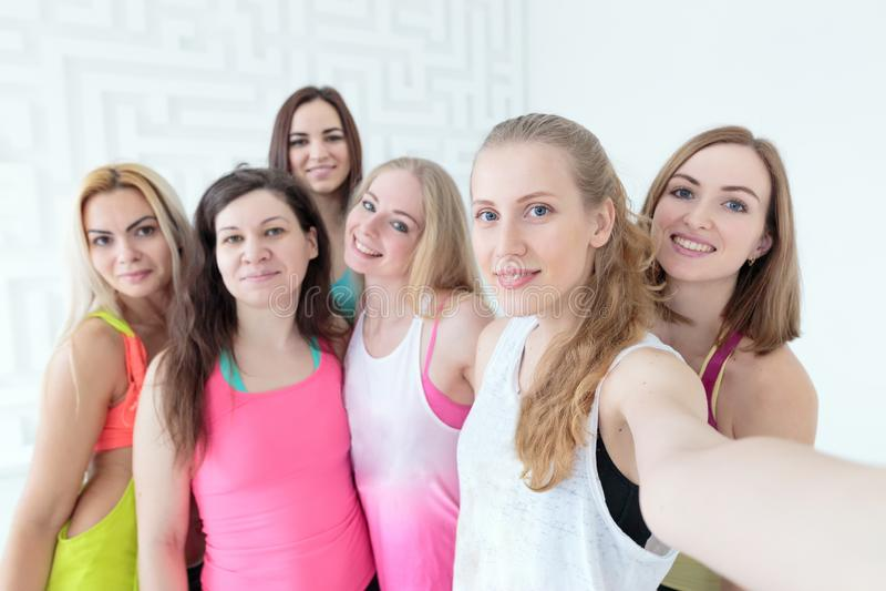 Группа в составе sporty счастливые женщины усмехаясь и принимая selfie стоковое фото