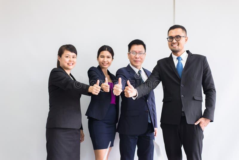 Группа в составе tumb рук людей дела азиатское вверх после встречи, представления успеха и семинара тренировать на офисе стоковое фото rf