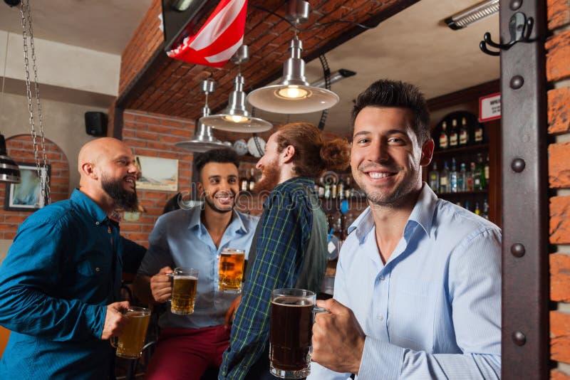 Группа в стеклах владением бара говоря, выпивая кружки человека пива, рубашки носки друзей гонки смешивания жизнерадостные стоковые изображения rf