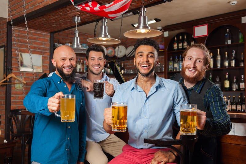 Группа в стеклах Clink бара провозглашать, выпивая кружки человека владением пива, рубашки носки друзей гонки смешивания жизнерад стоковое фото