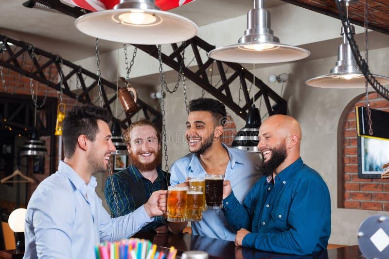 Группа в стеклах Clink бара провозглашать, выпивая кружки человека владением пива, рубашки носки друзей гонки смешивания жизнерад стоковые фотографии rf