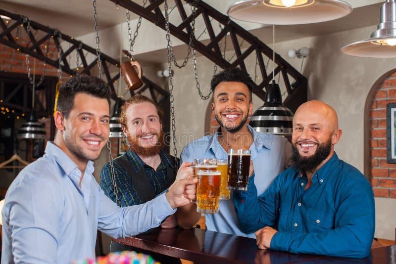 Группа в стеклах Clink бара провозглашать, выпивая кружки человека владением пива, рубашки носки друзей гонки смешивания жизнерад стоковые изображения rf