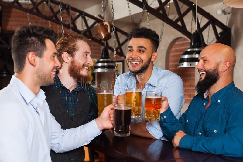 Группа в стеклах Clink бара провозглашать, выпивая кружки человека владением пива, рубашки носки друзей гонки смешивания жизнерад стоковая фотография rf