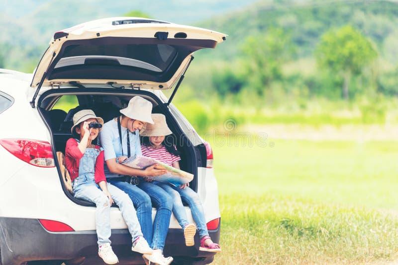 группа детей азиатской семьи проверяет карту и указывает на авто приключения и туризм для путешествия по месту назначения отдых п стоковые фото