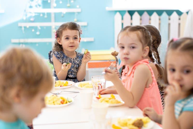 Группа детей, сидящих за столом с обедом и едящих закуски Дети ужинают в детском саду стоковые фото