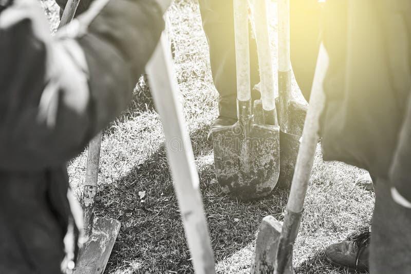 Группа или команда людей стоя на траве с тасовками в их руках готовых для трудной работы стоковые фотографии rf