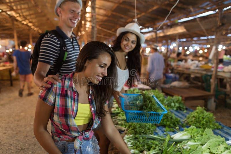 Группа людей выбирая Potherbs на продуктах покупки друзей уличного рынка счастливых усмехаясь совместно ходя по магазинам на экзо стоковая фотография