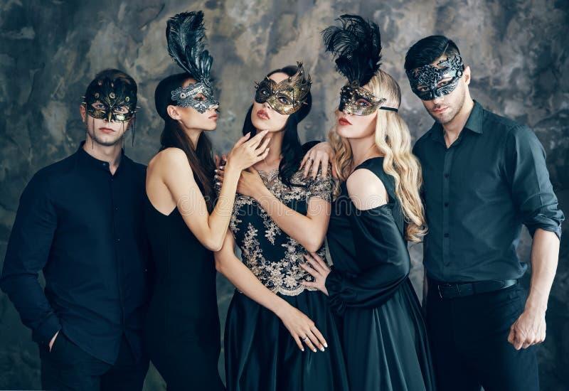 Группа людей в маске масленицы masquerade представляя в студии стоковое изображение rf