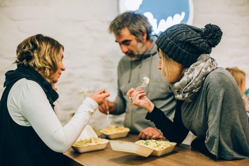 Группа людей ест макаронные изделия спагетти в ресторане фаст-фуда стоковое фото