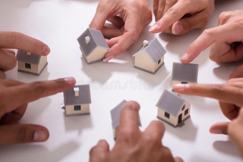 Группа людей касаясь миниатюрному дому стоковые фотографии rf