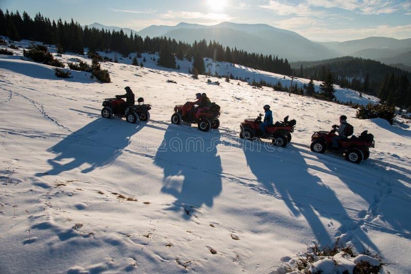 Группа людей наслаждаясь заходом солнца, на внедорожных 4-Уилерах ATV велосипед на снеге в горах в зиме стоковое фото rf