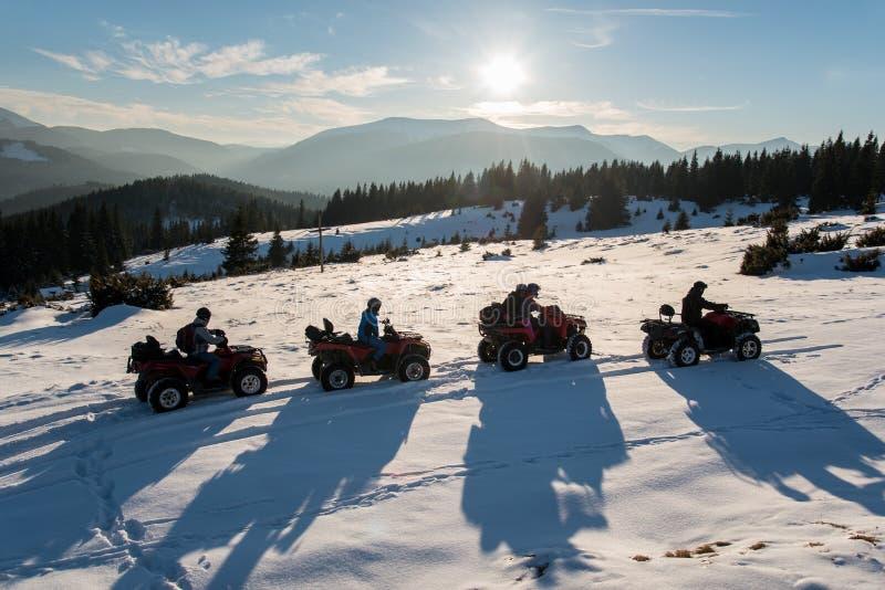Группа людей наслаждаясь заходом солнца на кваде велосипед на снеге в горах в зиме стоковое фото rf