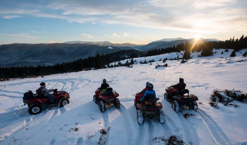 Группа людей на внедорожном кваде велосипед, наслаждающся красивым заходом солнца в горах в зиме стоковые фотографии rf