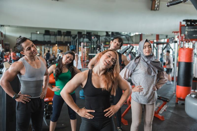 Группа людей на фитнес-центре протягивая для того чтобы нагревать стоковые фото