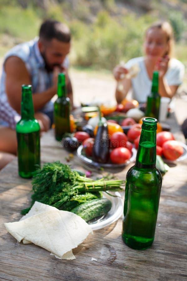 Группа людей обедая концепция единения Лучшие други выпивают вкусное пиво на пикнике лета стоковые фото