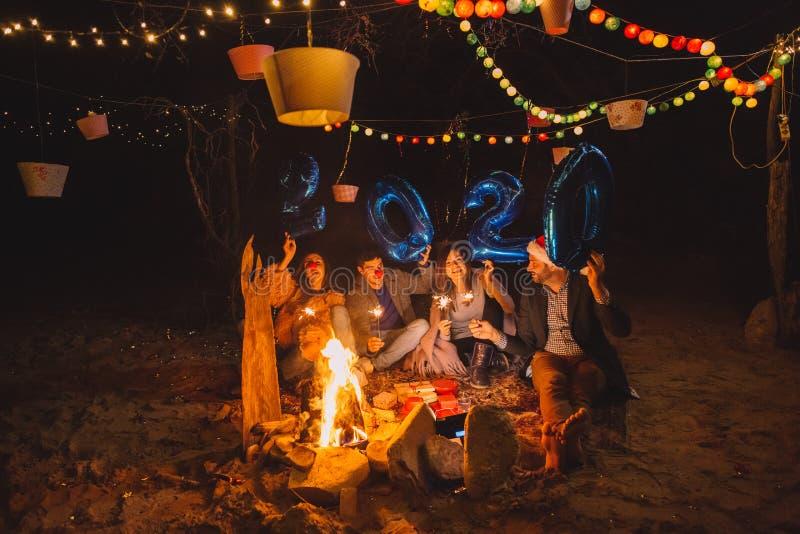Группа людей с шариками 2020 года, отмечающих Новый год на пляже Campfire стоковое фото rf