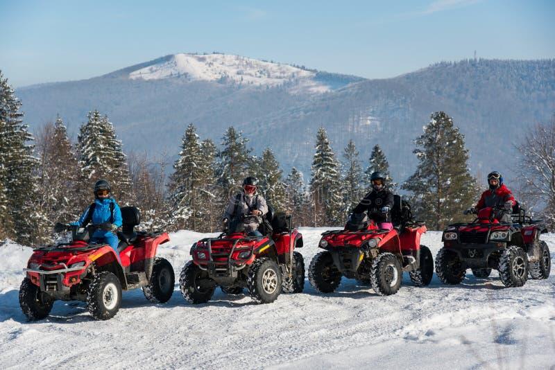 Группа людей управляя квадом велосипед наверху горы в зиме стоковые фото
