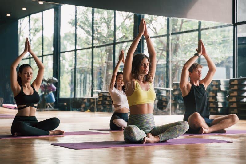 Группа молодых людей, практикующих йогу В молитвенном положении и подняли руки, сидя на мате в тренажерном зале, Понятие релаксац стоковые фотографии rf