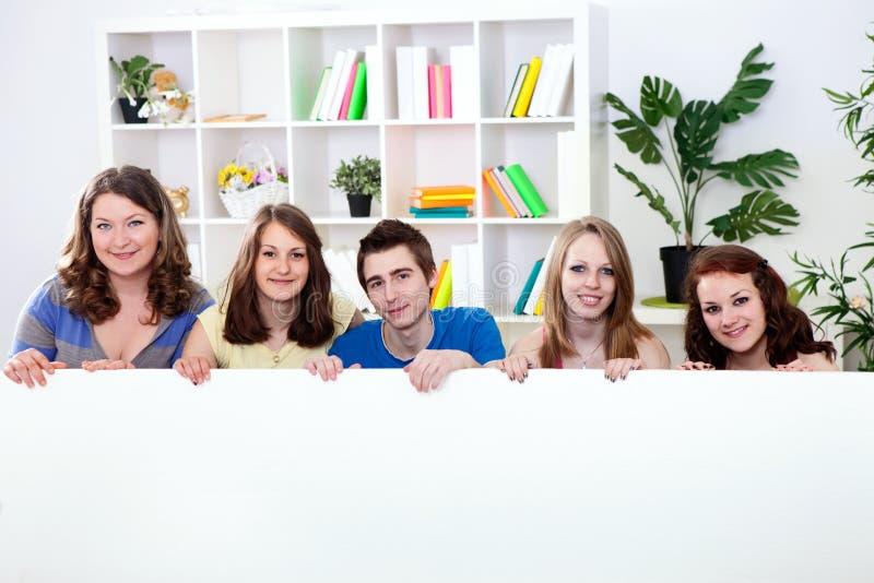 Группа подростка держа большую пустую бумагу стоковые изображения rf