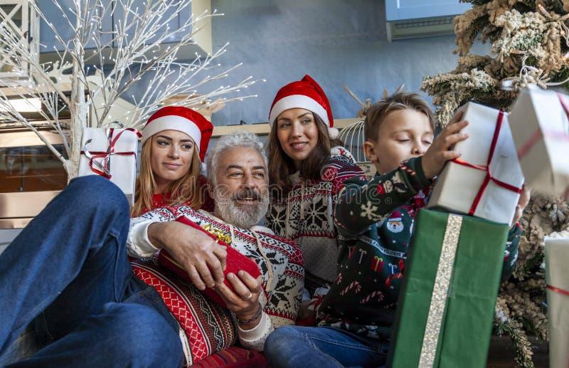 Группа семьи под полночью рождественской елки ждать стоковые фотографии rf