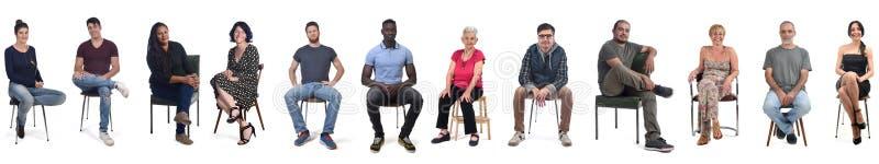 Группа смешанных людей, сидящих на белом стоковые фото