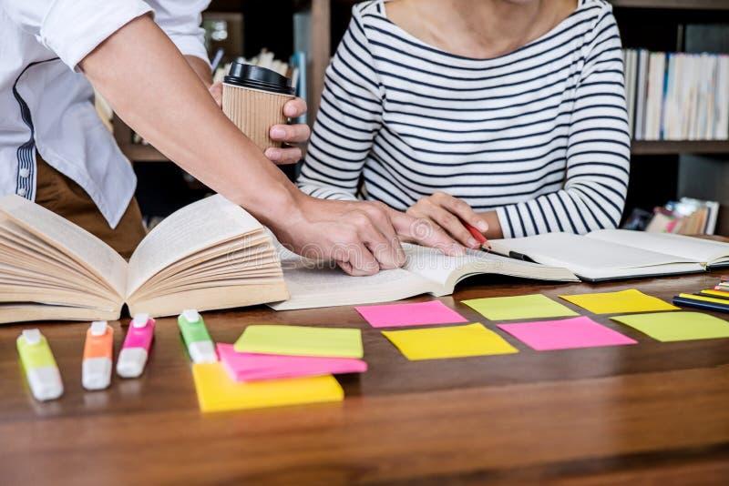 Группа средней школы или студента колледжа сидя на столе в библиотеке изучая и читая, делающ подготовку практики домашней работы  стоковое фото