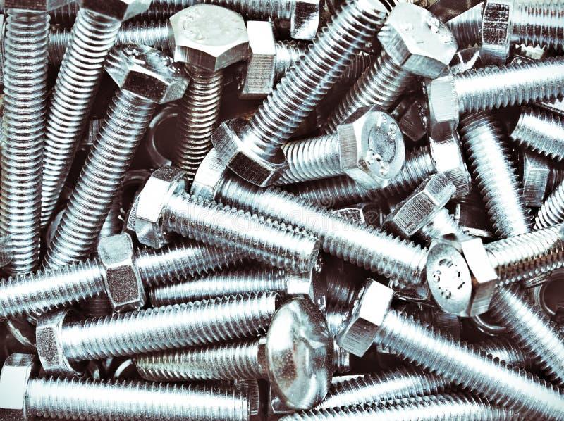 Группа стальных стальных болтов промышленного производства, цинковый кучи хром Темно-промышленный контрастный фон стоковые фото