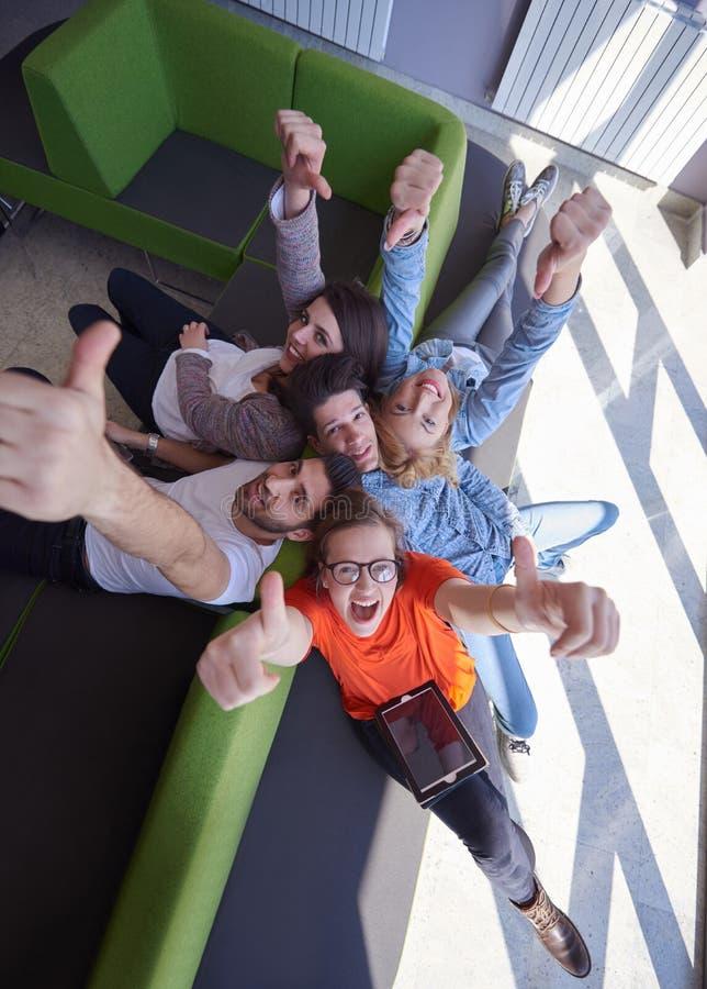 Группа студентов работая на проекте школы совместно стоковое изображение