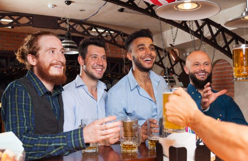 Группа человека в стеклах пива владением бара, стоя на бармене встречного заказа, друзья гонки смешивания жизнерадостные стоковые изображения rf