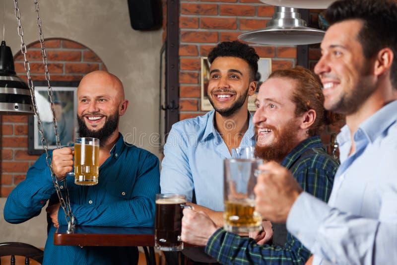 Группа человека в усмехаясь бара счастливом и наблюдая футболе, выпивая кружках владением пива, друзьях гонки смешивания жизнерад стоковые фото