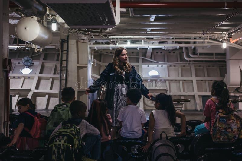 Группа школьников слушая проводника во время путешествия внутри Intrepi стоковое фото