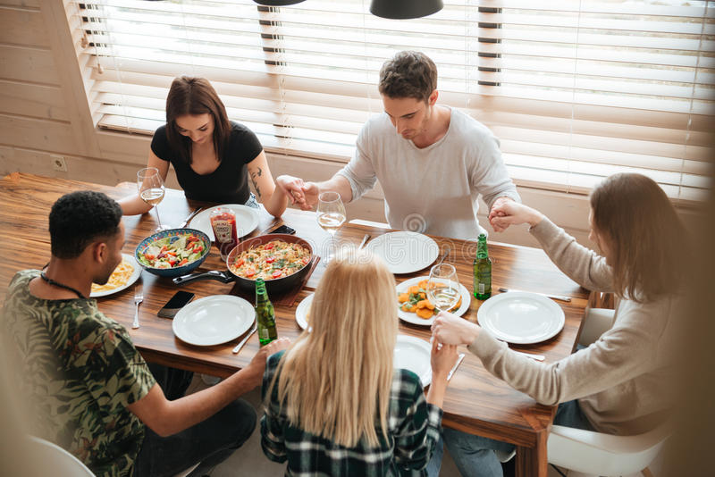 Группа людей держа руки и моля на обеденном столе стоковая фотография rf