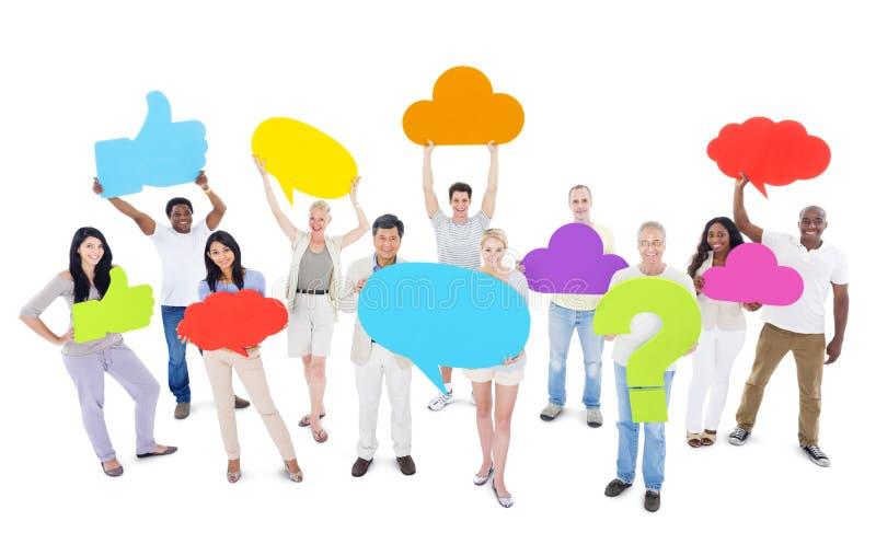 Группа людей деля идеи и держа социальные значки средств массовой информации стоковое изображение